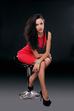 La giovane donna castana splendida sexy in vestito rosso sulla sedia, è Immagine Stock Libera da Diritti