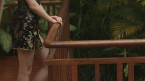 La giovane donna castana sta sul terrazzo stock footage