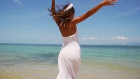 La giovane donna castana in una corona bianca del fiore e del vestito funziona a piedi nudi lungo il litorale e si gode di che fi archivi video