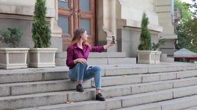 La giovane donna casuale prende il selfie con il telefono che si siede sui punti della costruzione stock footage