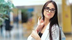 La giovane donna caucasica attraente che posa con l'acquisto insacca nel centro commerciale stock footage