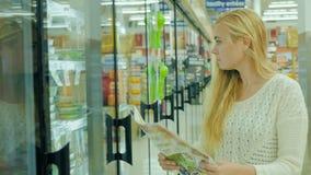 La giovane donna caucasica compra l'alimento Legge gli sconti di pubblicità a mezzo stampa, quindi prende il prodotto dal frigori stock footage