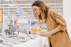 La giovane donna caucasica con una compressa seleziona il pesce in un supermercato Fotografia Stock Libera da Diritti