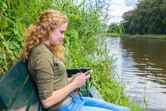 La giovane donna caucasica fa funzionare il telefono cellulare Immagini Stock