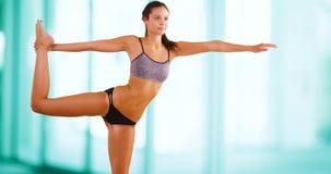 La giovane donna caucasica fa l'yoga alla palestra Fotografia Stock