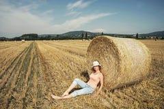 La giovane donna caucasica gode dell'estate davanti alla pila di Fotografie Stock Libere da Diritti