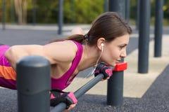 La giovane donna caucasica negli abiti sportivi luminosi inserisce sullo sportground all'aperto Cuffie bianche, guanti protettivi immagine stock