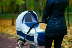 La giovane donna caucasica sta spingendo la carrozzina bianca mentre lei che cammina al parco di autunno con le belle foglie gial Fotografia Stock