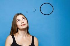 La giovane donna causacian con gli occhi azzurri su pensa o sogna di qualcosa immagine stock