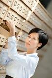 La giovane donna cerca qualcosa nel catalogo di scheda Immagine Stock