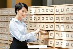 La giovane donna cerca qualcosa nel catalogo di scheda Immagini Stock