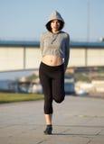 La giovane donna che allunga la gamba muscles all'aperto Immagini Stock Libere da Diritti