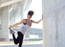 La giovane donna che allunga la gamba muscles all'aperto Fotografia Stock