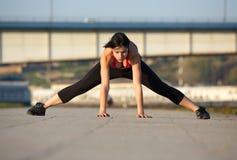 La giovane donna che allunga la gamba muscles con le mani sul pavimento Immagine Stock Libera da Diritti