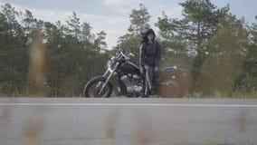 La giovane donna che cambia le sue scarpe che si siedono sulla sua bici sulla strada La ragazza che mette sulle scarpe con i tacc stock footage
