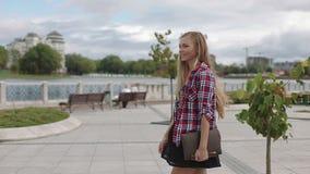 La giovane donna che cammina con il computer portatile nel parco della città passa dalla macchina fotografica stock footage