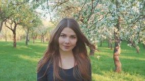 La giovane donna che cammina in un meleto in primavera fiorisce il bianco Ritratto di bella ragazza nella frutta di sera stock footage