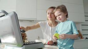 La giovane donna che cucina le cialde in cucina ed in ragazzo sveglio la aiuta Famaly che cucina prima colazione nelle prime ore  archivi video