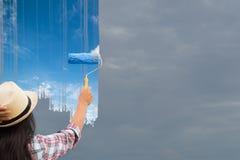 La giovane donna che dipinge il cielo grigio diventa blu fotografia stock libera da diritti