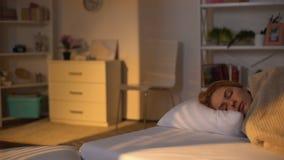 La giovane donna che dorme a letto nell'ambito della luce solare di mattina, resto di fine settimana, si sveglia tardi stock footage