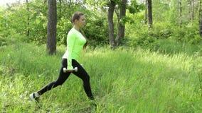 La giovane donna che esercita fare si accovaccia con i dumbbels in parco archivi video