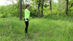 La giovane donna che esercita fare si accovaccia con i dumbbels in parco stock footage