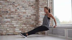 La giovane donna che fa gli sport si esercita per rinforzare i muscoli delle mani video d archivio