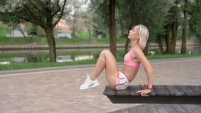 La giovane donna che fa l'ABS sgranocchia in parco su un banco archivi video