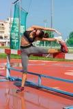 La giovane donna che fa l'addestramento di forma fisica nel locale mette in mostra lo stadio all'aperto Immagine Stock