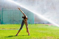 La giovane donna che fa l'addestramento di forma fisica nello stadio di sport del locale si batte Fotografie Stock Libere da Diritti