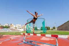 La giovane donna che fa l'addestramento di forma fisica nello stadio di sport del locale si batte Immagini Stock Libere da Diritti