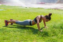 La giovane donna che fa l'addestramento di forma fisica nello stadio di sport del locale si batte Immagini Stock