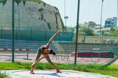 La giovane donna che fa l'addestramento di forma fisica nello stadio di sport del locale si batte Fotografia Stock Libera da Diritti