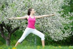 La giovane donna che fa l'allungamento si esercita all'aperto Fotografia Stock