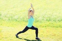 La giovane donna che fa l'allungamento si esercita su erba di estate Fotografia Stock Libera da Diritti