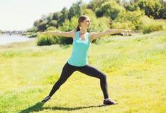 La giovane donna che fa l'allungamento si esercita su erba nel giorno di estate Fotografia Stock Libera da Diritti