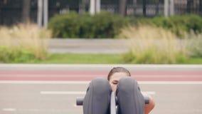 La giovane donna che fa l'esercizio di forma fisica sull'allenamento ha frantumato nel parco dell'estate stock footage