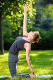 La giovane donna che fa l'yoga si esercita nel parco della città dell'estate Fotografie Stock