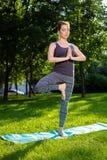 La giovane donna che fa l'yoga si esercita nel parco della città dell'estate Immagine Stock Libera da Diritti