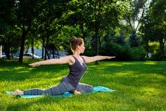 La giovane donna che fa l'yoga si esercita nel parco della città dell'estate Immagini Stock Libere da Diritti