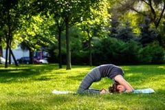 La giovane donna che fa l'yoga si esercita nel parco della città dell'estate Immagine Stock