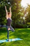 La giovane donna che fa l'yoga si esercita nel parco della città dell'estate Immagini Stock
