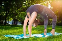 La giovane donna che fa l'yoga si esercita nel parco della città dell'estate Fotografie Stock Libere da Diritti