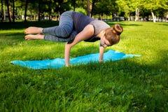 La giovane donna che fa l'yoga si esercita nel parco della città dell'estate Fotografia Stock Libera da Diritti