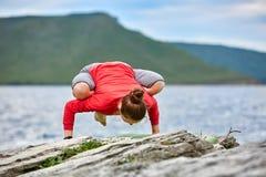 La giovane donna che fa l'yoga si esercita sul grande fiume vicino di pietra contro bello paesaggio Immagine Stock