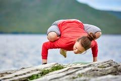 La giovane donna che fa l'yoga si esercita sul grande fiume vicino di pietra contro bello paesaggio immagini stock libere da diritti