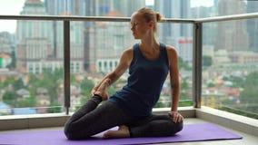 La giovane donna che fa l'yoga si esercita sul suo balcone in costruzione multipiana con una vista su una città con gli skycrappe stock footage