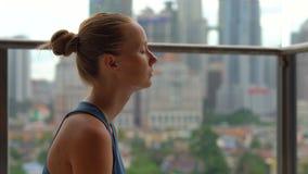 La giovane donna che fa l'yoga si esercita sul suo balcone in costruzione multipiana con una vista su una città con gli skycrappe video d archivio