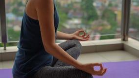 La giovane donna che fa l'yoga si esercita sul suo balcone in costruzione multipiana con una vista su una città con gli skycrappe archivi video