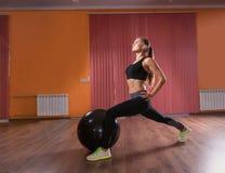 La giovane donna che fa la gamba dà una stoccata nello studio di esercizio Immagine Stock Libera da Diritti